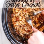 two hands holding forks pulling crockpot salsa chicken apart