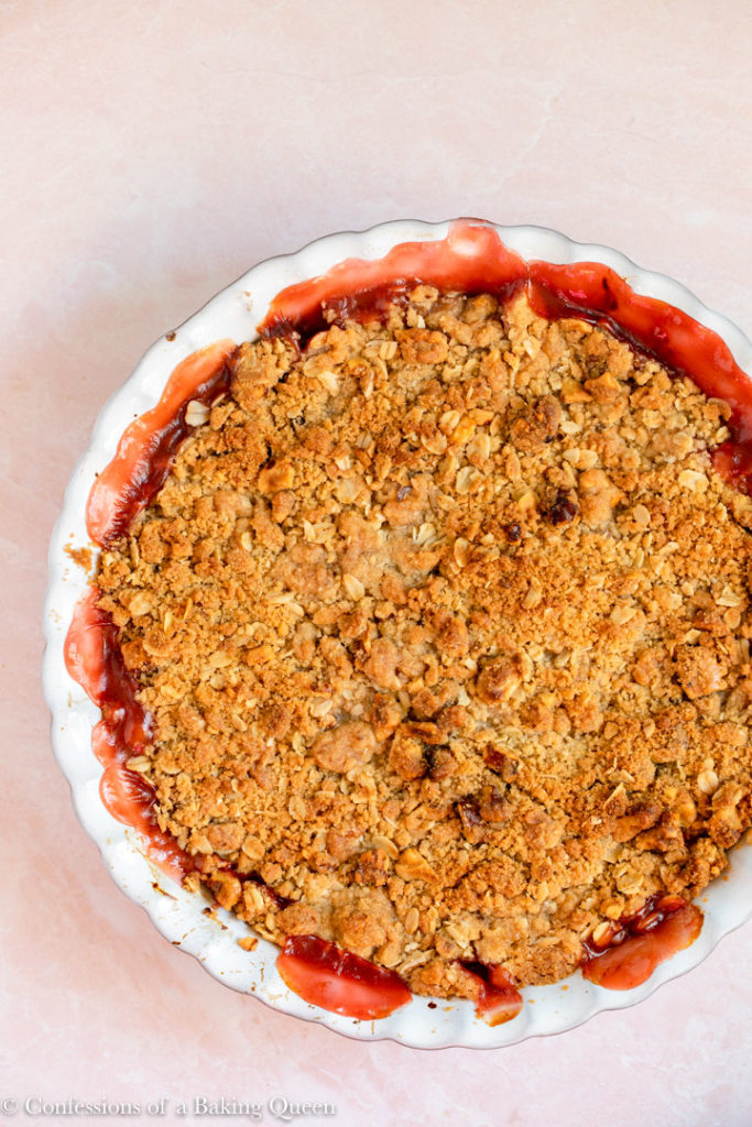 rhubarb crisp just baked to golden perfection on a pink surface