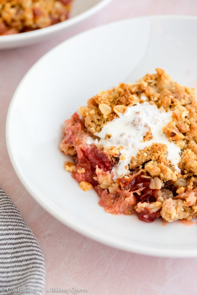 cream served on top of rhubarb crisp on a pink surface with a white and blue stripped linen