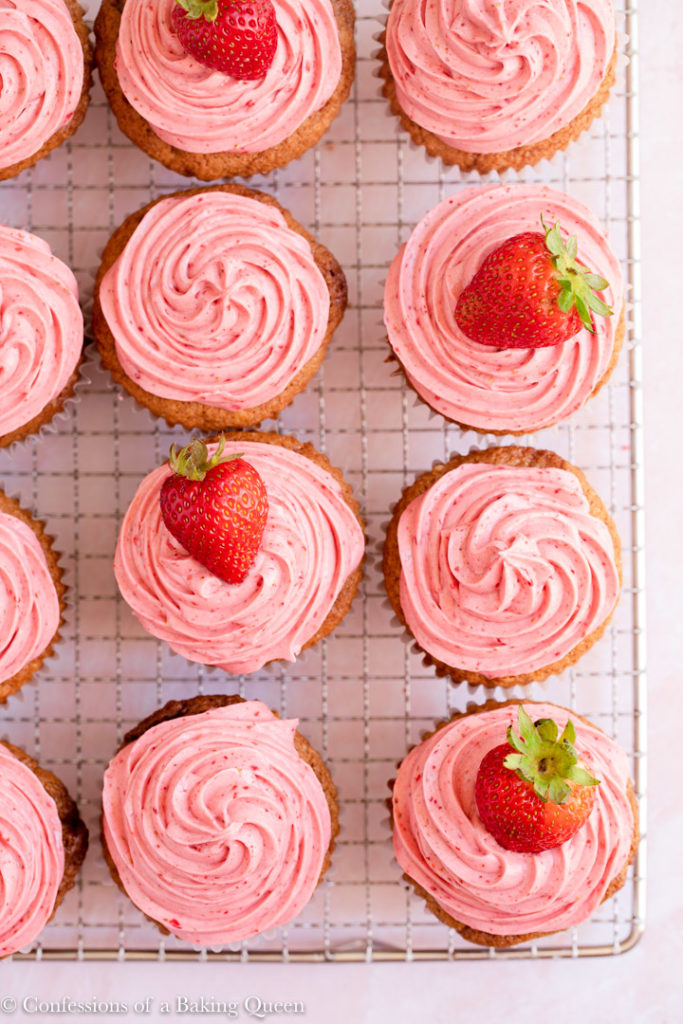 strawberry cupcakes topped with fresh strawberries on a wire rack