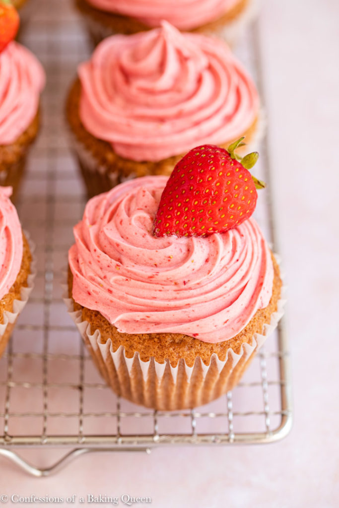 close up of a strawberry decorated strawberry cupcake on a wire rack