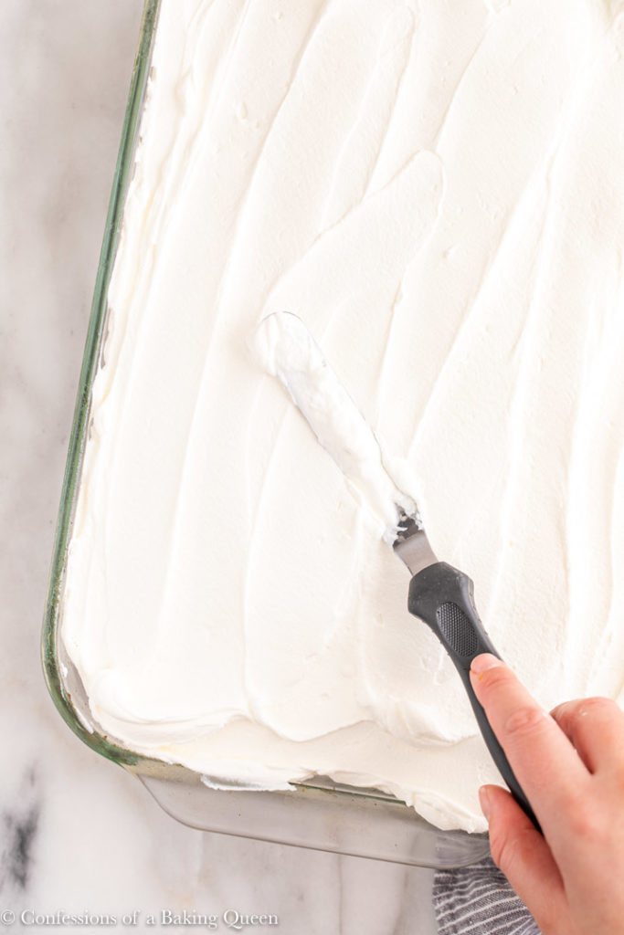 hand holding angled spatula spreading whipped cream on top of better than sex chocolate cake