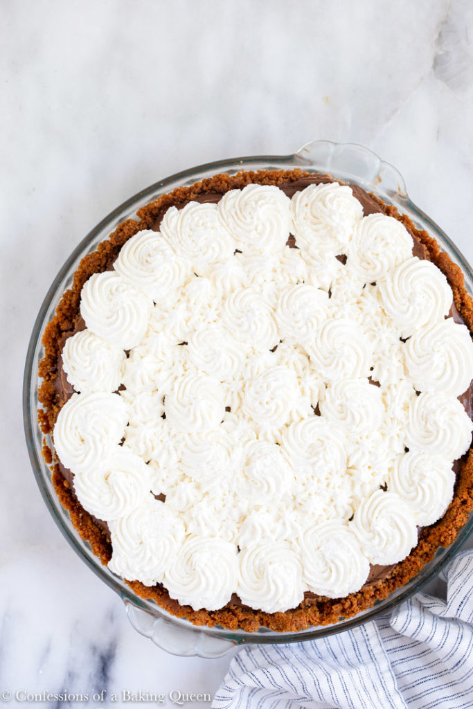 chocolate pudding pie with whipped cream on a white marble surface with a white and grey linen