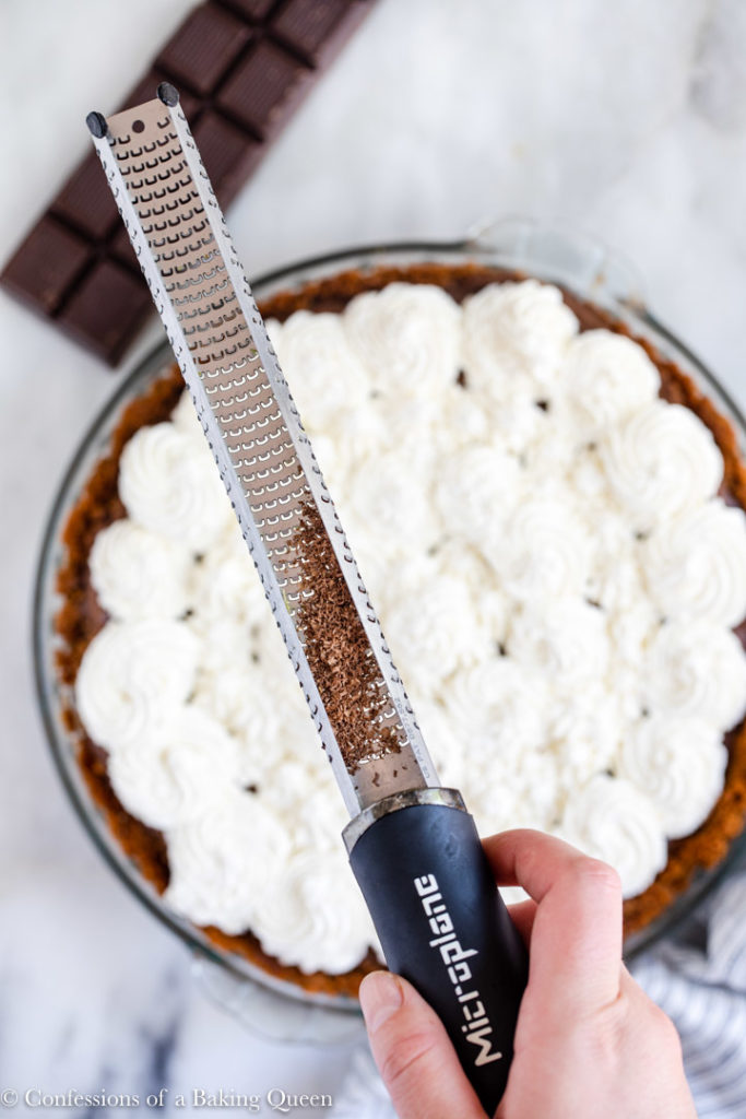 zester with chocolate pieces on top of whipped cream topped chocolate pudding pie on a white marble surface