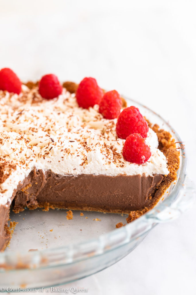 chocolate pudding pie in a glass pie dish with a chunk missing