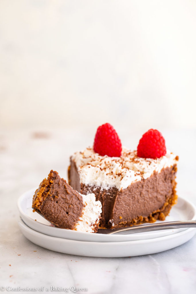 fork holding a piece of chocolate pudding pie on a white plate