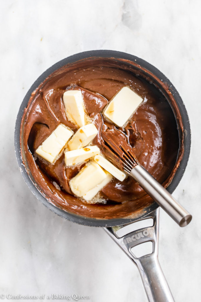 chunks of butter added to chocolate pudding mixture in a small pot