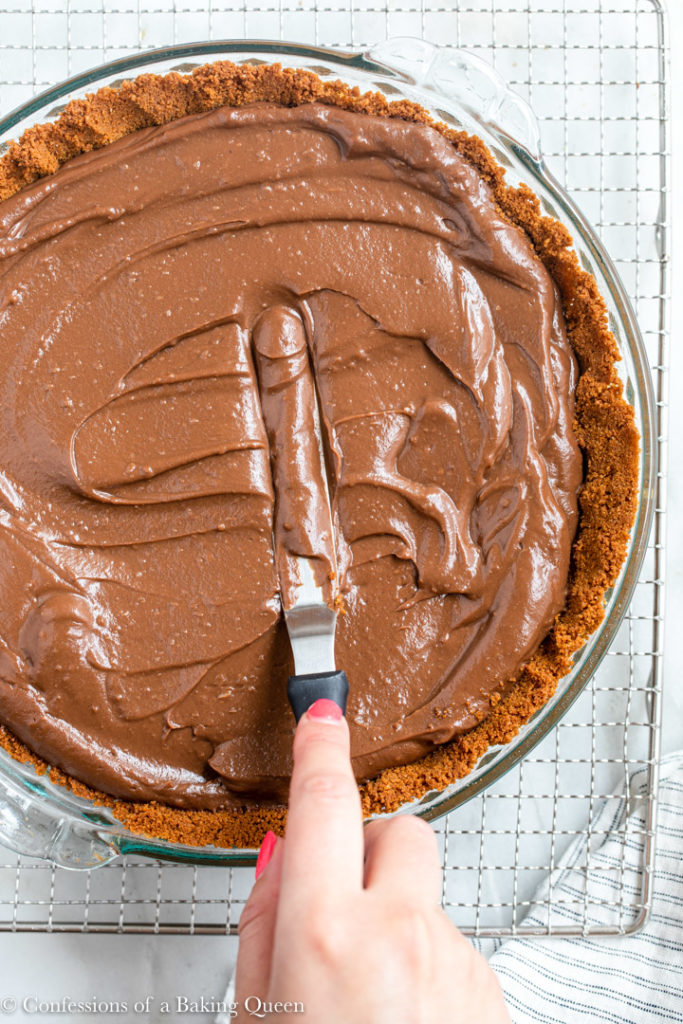 hand holding an angled spatula spreading the chocolate pudding into pie crust