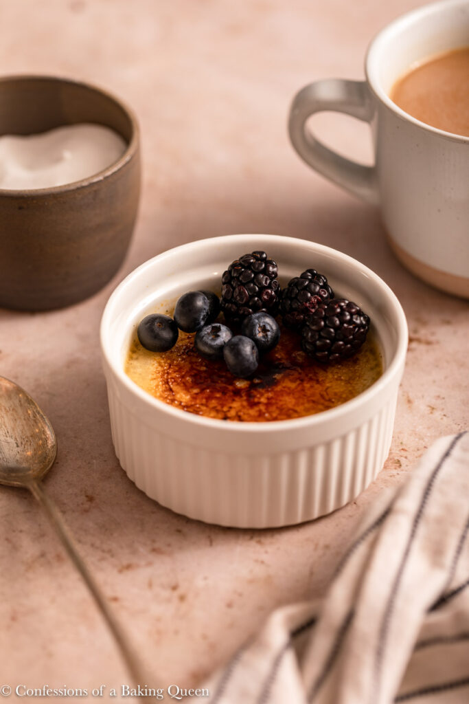 coffee creme brulee with a cup of coffee and spoon and white and blue linen on a light brown surface