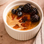 coffee creme brulee with berries half eaten next to a bowl of blueberries and a white and blue stripped on a light brown surface