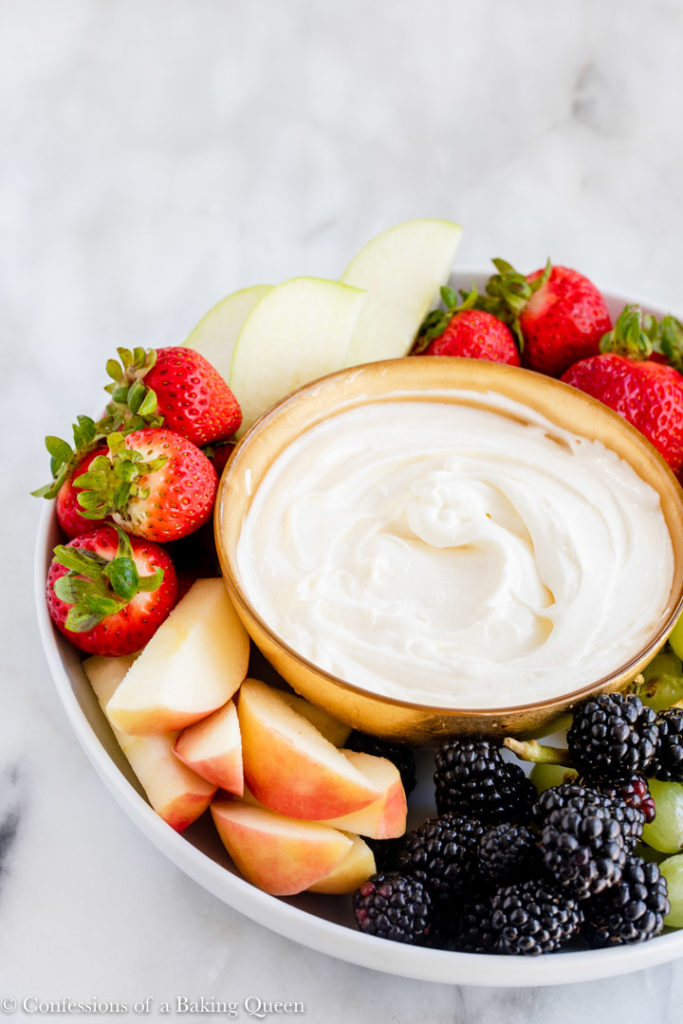 gold bowl full of cream cheese dip on a platter with fruit