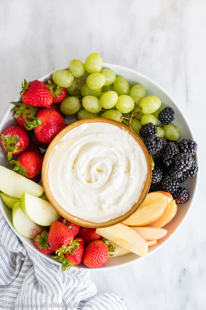 sweet cream cheese dip next to lots of fruit on a white platter