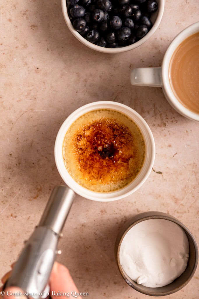 kitchen torch bruleeing the top of a coffee creme brulee next to a cup of sugar, bowl of blueberries and cup of coffee on a light brown surface