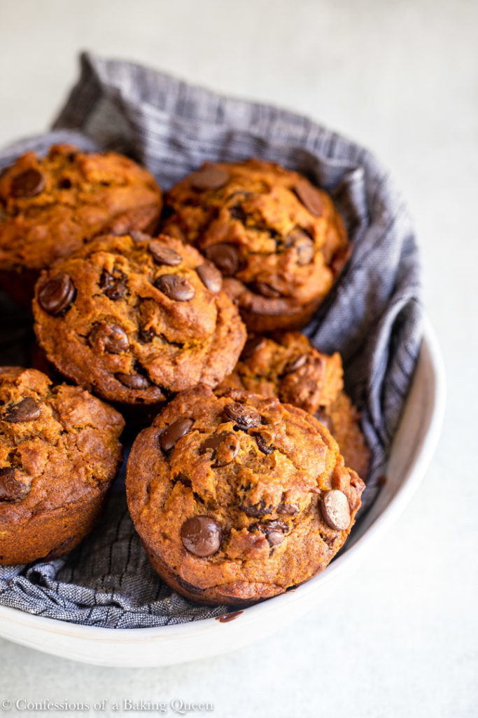 pumpkin chocolate chip muffins in a blue cloth lined bowl