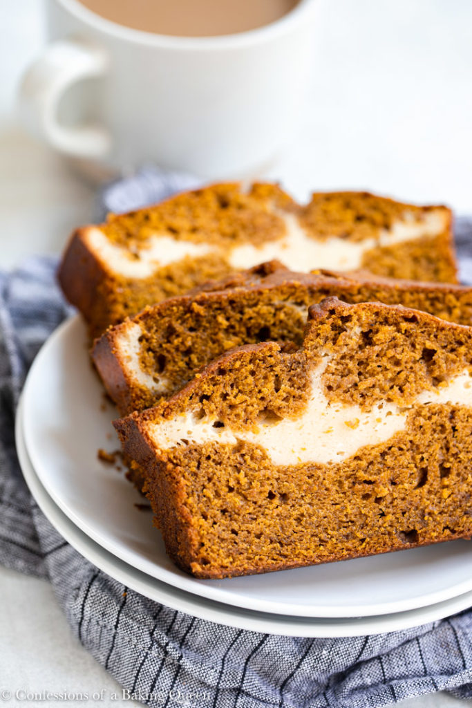 pumpkin cream cheese bread slices on a white plate on a white surface with a blue linen