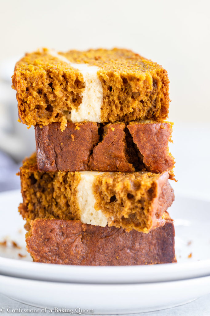 cream cheese pumpkin bread pieces cut in half stacked on a white plate