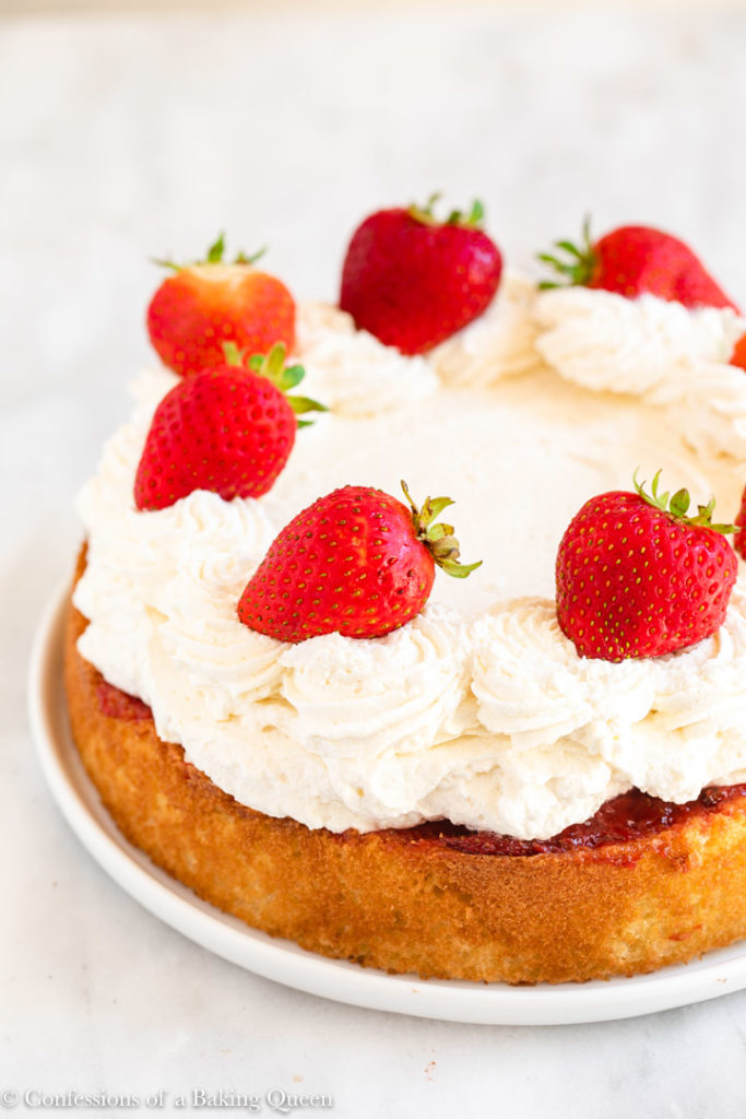 strawberry topped strawberry poke cake on a white plate