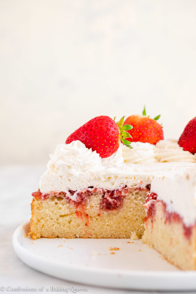 strawberry poke cake cut open on a white plate