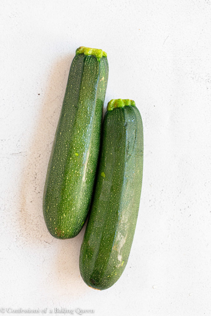 two zucchinis on a light grey surface
