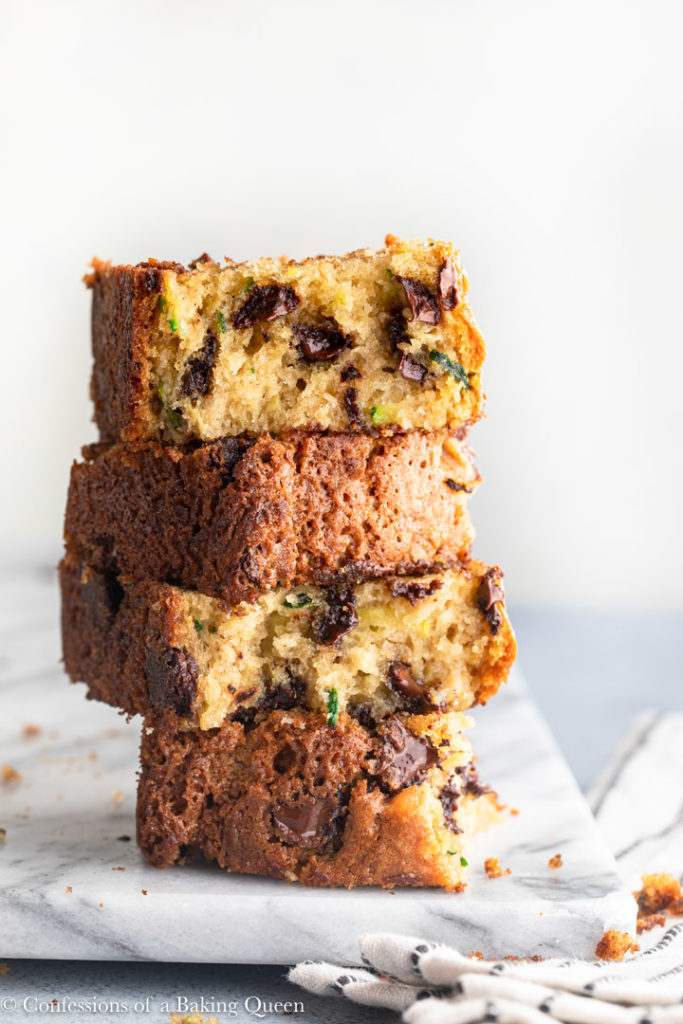 Chocolate Chip Zucchini Bread pieces stacked on top of each other on a marble slab on a grey surface with a white and blue line