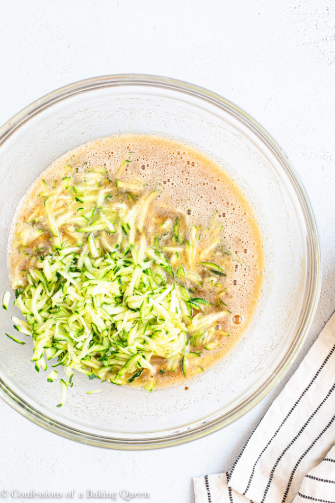 zucchini added to cake ingredients in a glass bowl on a grey surface with a white and blue line
