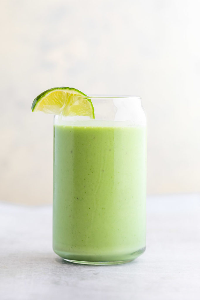 key lime smoothie in a glass with a lime wedge