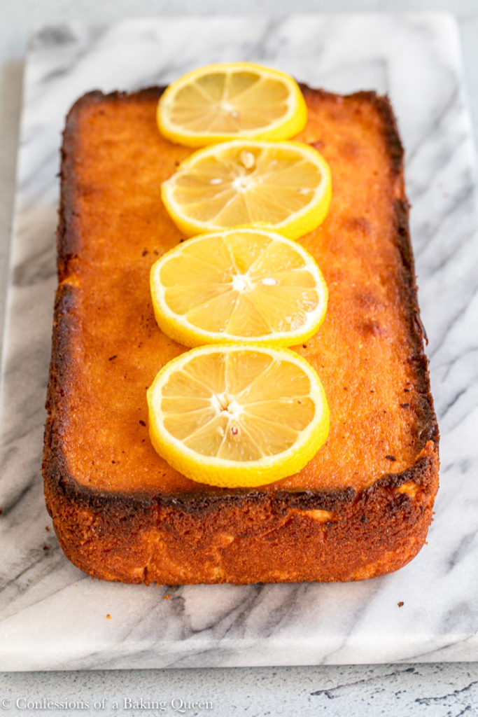 lemon pound cake sitting on a piece of marble on a grey surface