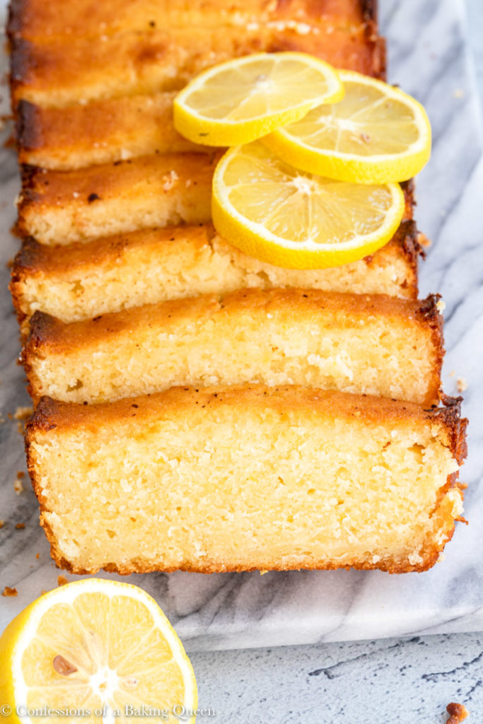 slices of lemon pound cake with lemon slices on top on a marble surface