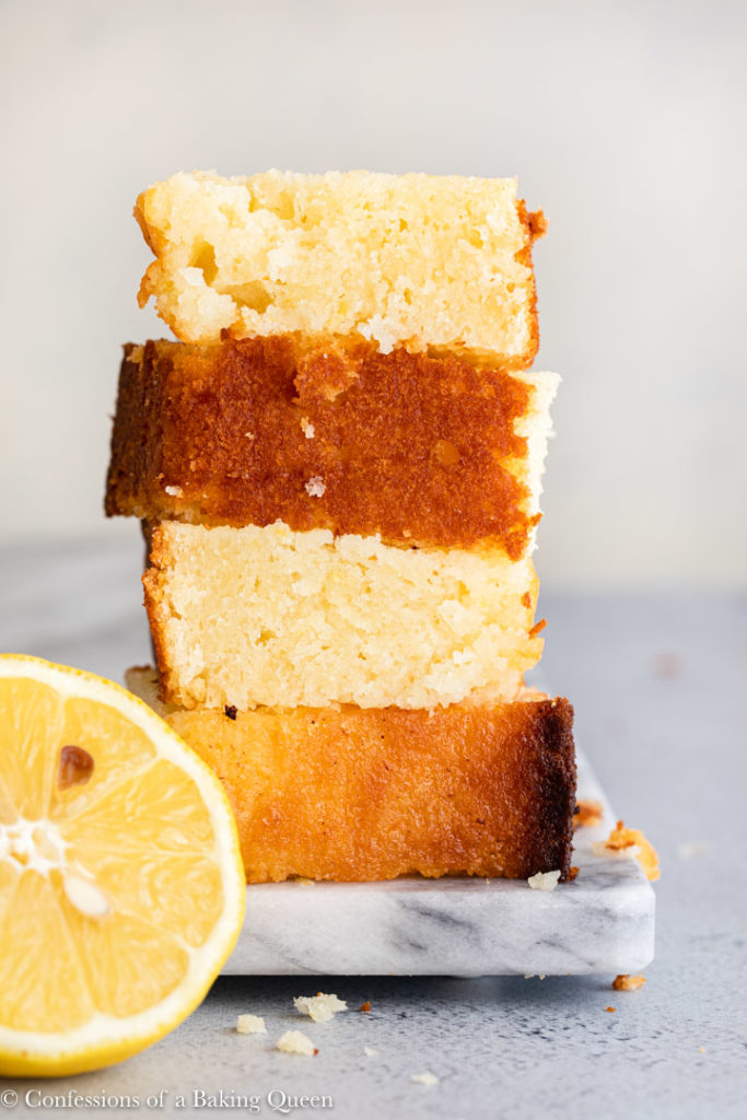 pieces of lemon pound cake stacked on top of each other on a marble surface on a grey surface