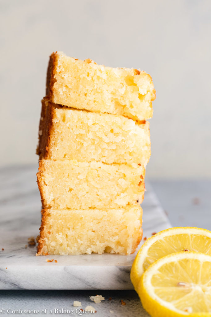 4 pieces of lemon loaf cake stacked on top of each other on a piece of marble on a grey surface