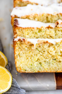 slices of lemon zucchini cake on a marble board