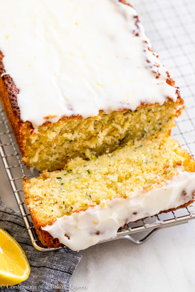 a slice of lemon zucchini cake falling off the loaf on a wire rack on a white surface with a blue linen