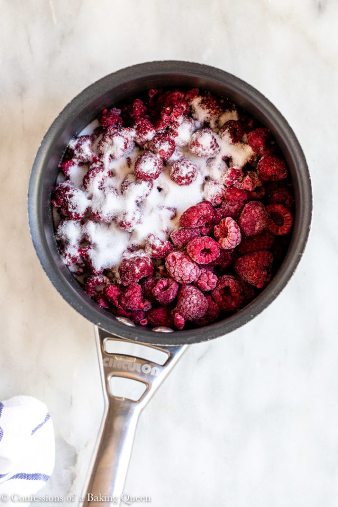 frozen raspberries and sugar in a small saucepan on a white surface