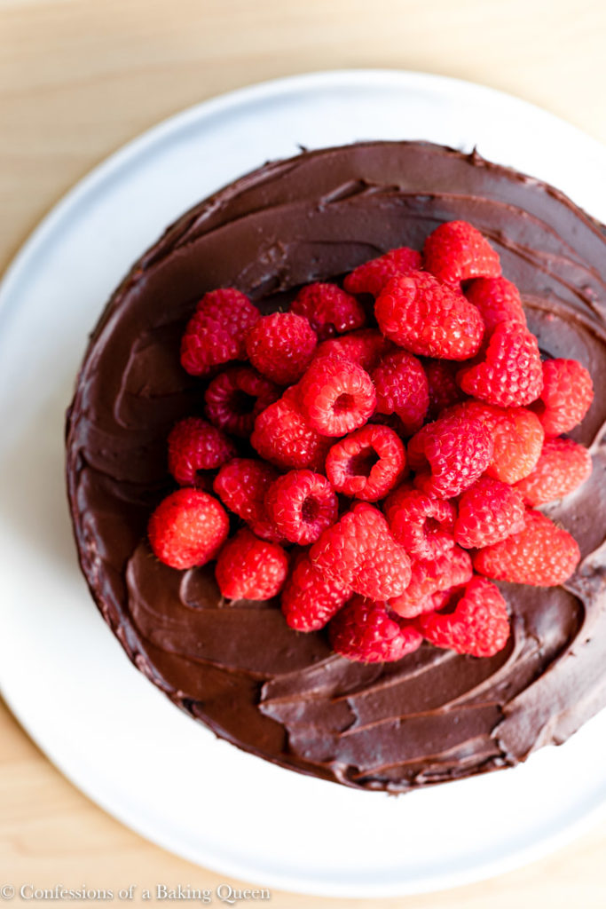 raspberry chocolate cake on a white serving platter on a wood surface