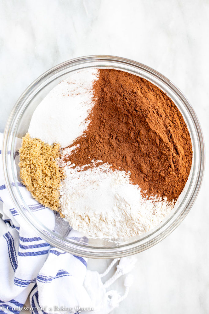 dry ingredients for a chocolate cake in a large glass bowl