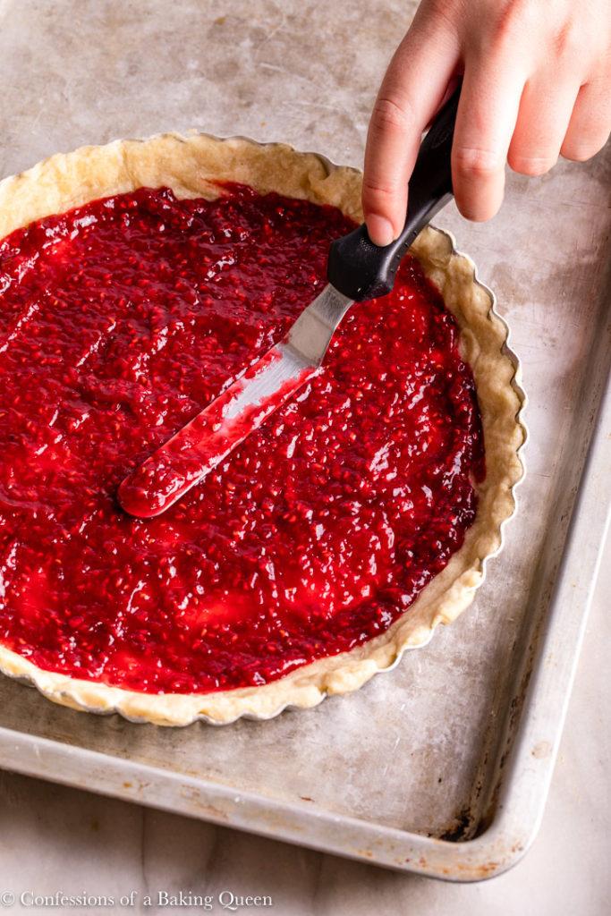 hand spreading raspberry jam in a sweet shortcrust pastry tart