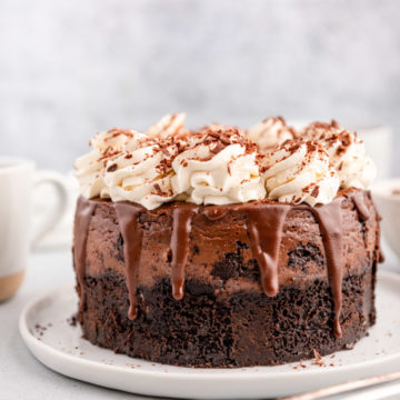chocolate cheesecake on a white plate with a cup of coffee in the background with some silverware on a grey background