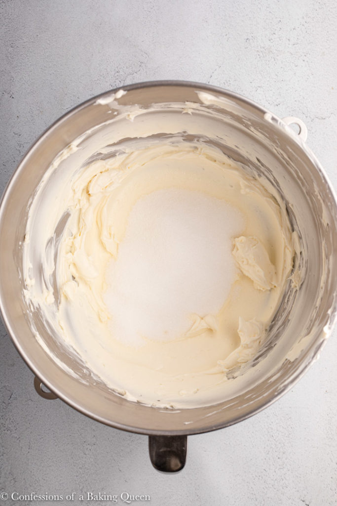 whipped cream cheese and sugar in a metal bowl