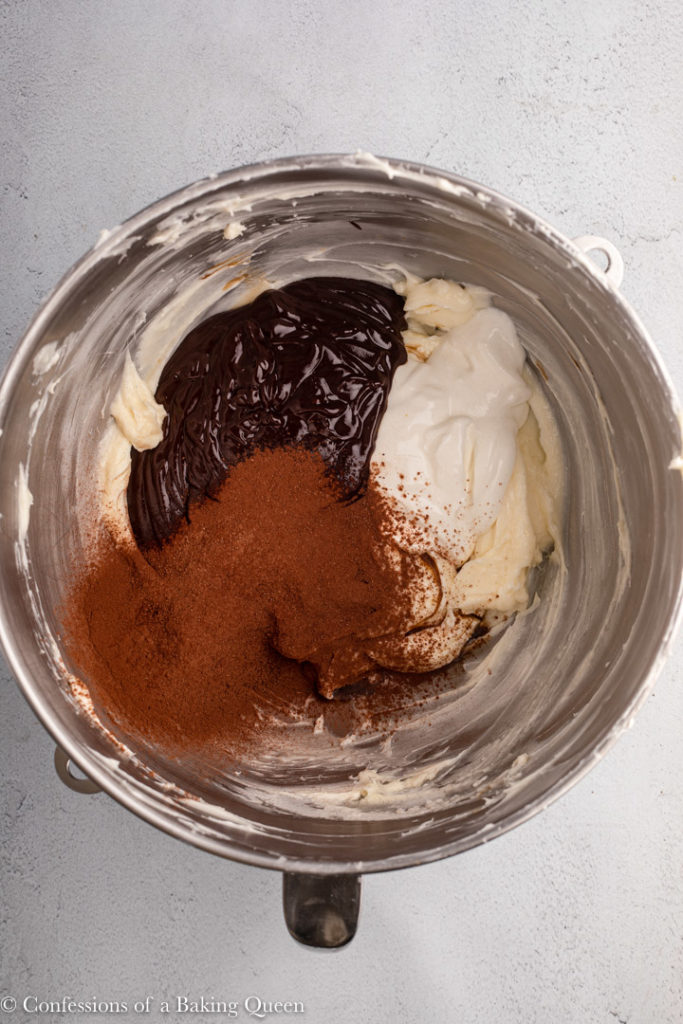 chocolate, cocoa powder, and sour cream added to cheesecake batter in a large bowl