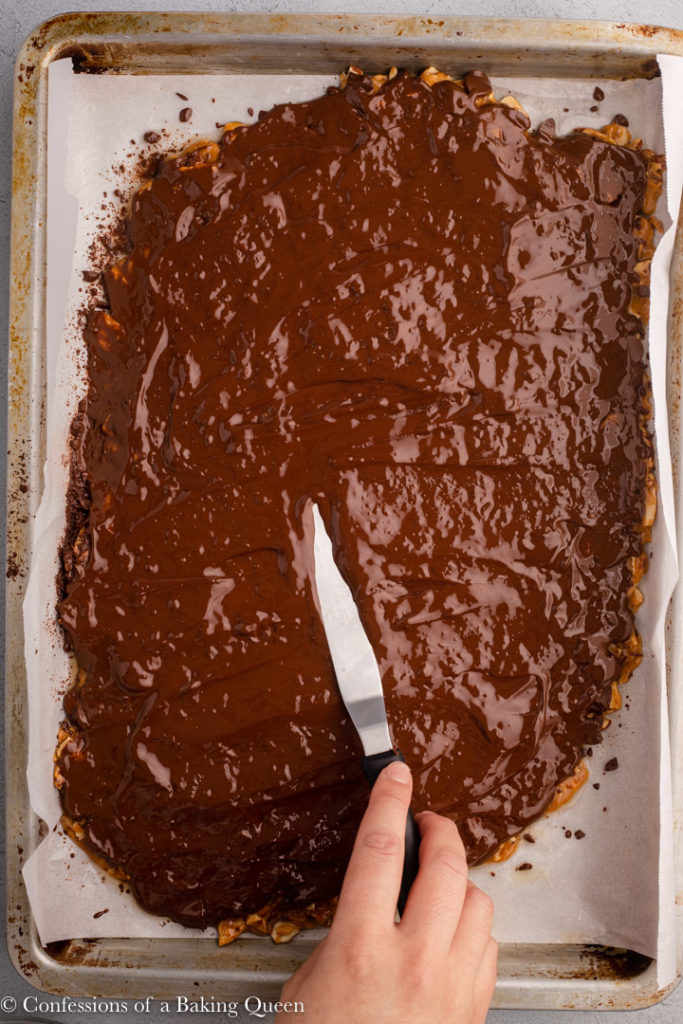 hand with an offset spatula spreading chocolate on top of toffee