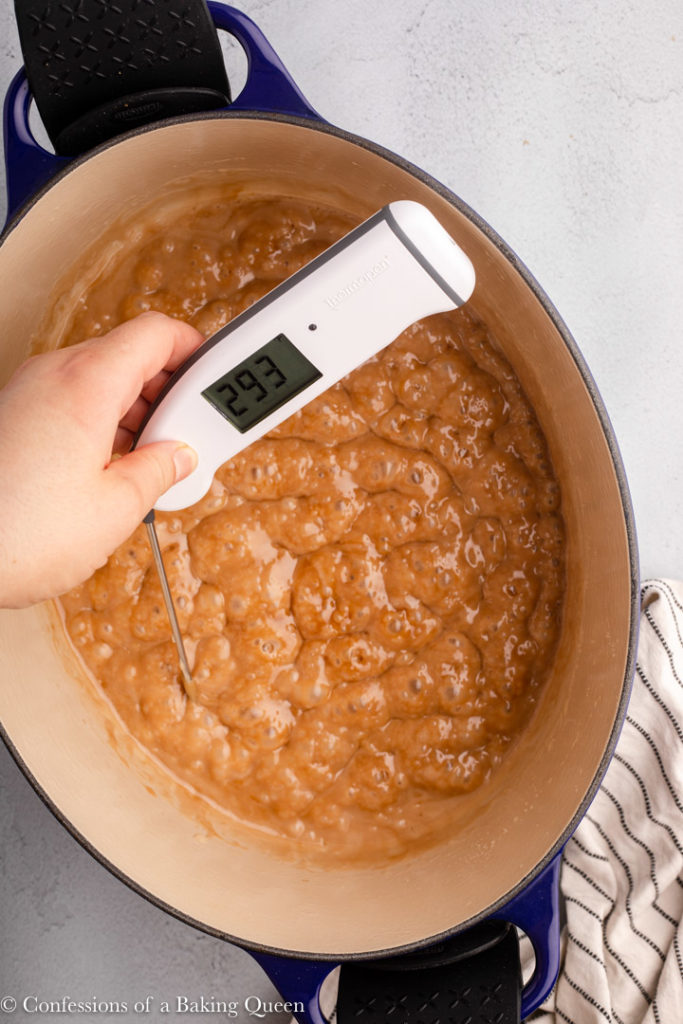 hand holding an instant read thermometer into butter toffee