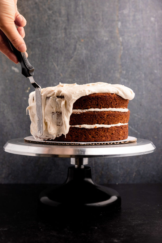 hand holding an angled spatula spreading frosting on an apple cake