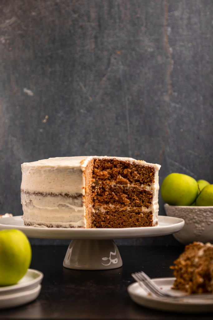 apple layer cake on a white cake stand next to a bowl of apples