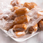 chewy caramels wrapped on a white plate on a white surface with a blue and white stripped linen