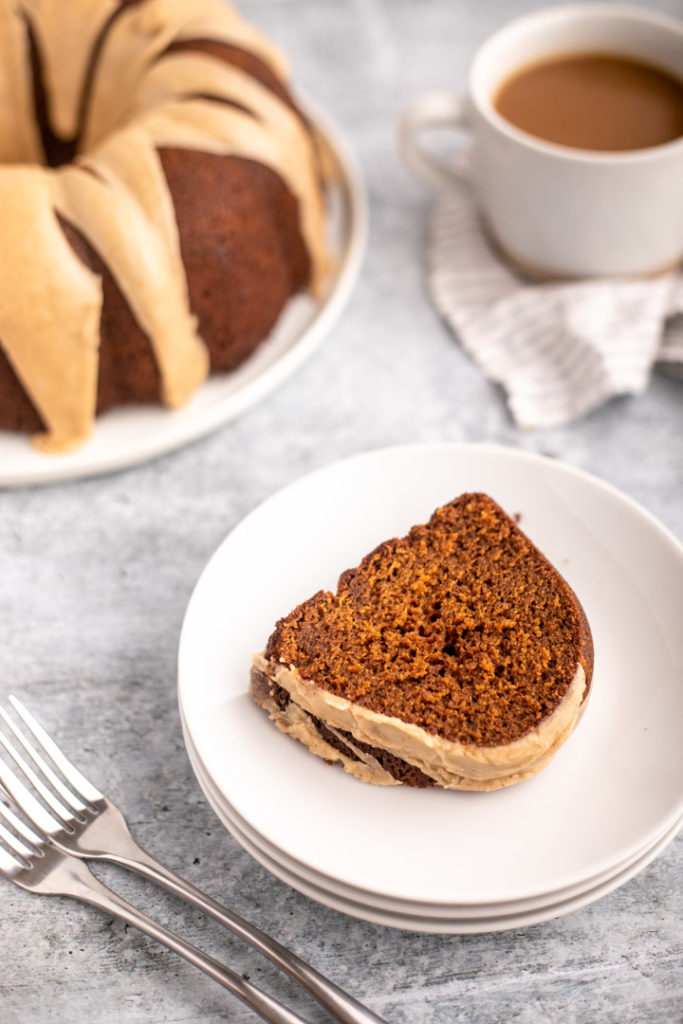slice of gingerbread bundt cake on a white plate with a cup of coffee