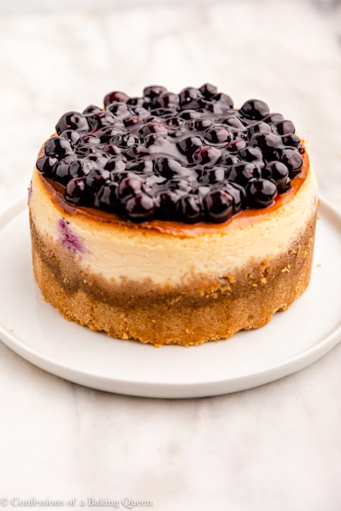 blueberry sauce spread out on a baked lemon cheesecake