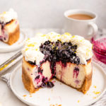 lemon blueberry cheesecake cut open on a plate next to a cup of tea and a slice of cheesecake