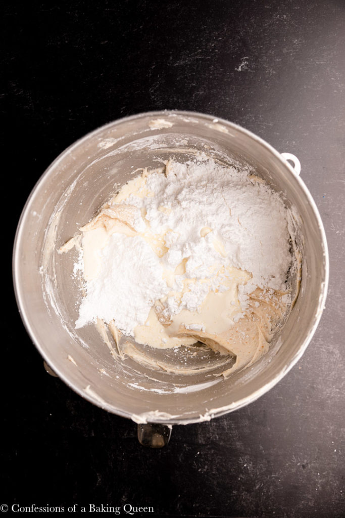heavy cream and powdered sugar added to brown butter cream cheese frosting in a large mixing bowl