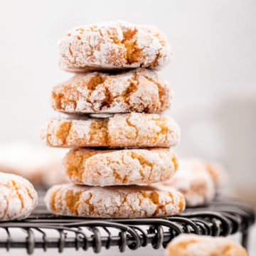 five amaretti cookies stacked on a black wire rack