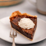 slice of chocolate chess pie with whipped cream on a plate